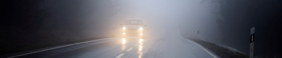 Dense fog on the country road, oncoming traffic